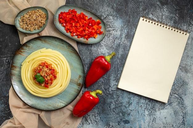 Vista de cima de um prato azul com saborosa refeição de massa servida com tomate e carne em uma toalha cor de bronze picada e pimentões inteiros e caderno espiral