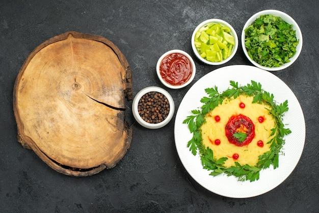 Vista de cima de um prato de batata frita com verduras no escuro