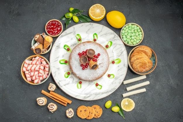 Vista de cima de um prato de bolo com frutas cítricas, biscoitos, geleia, doces