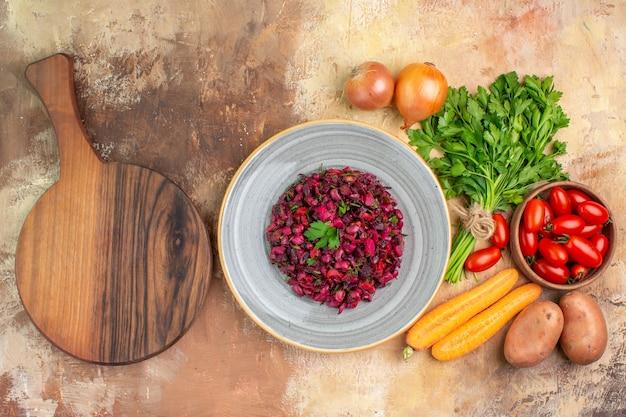 Vista de cima de um prato de cerâmica com deliciosa salada caseira e ingredientes para sua preparação em um fundo de madeira com espaço de cópia