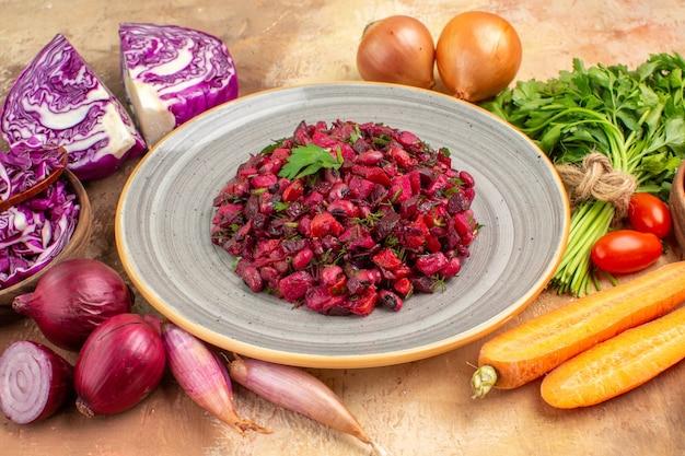 Vista de cima de um prato de cerâmica com salada de beterraba fresca e ingredientes para seu preparo em uma mesa de madeira