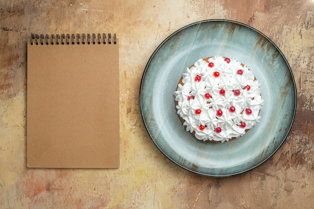 Vista de cima de um saboroso bolo decorado com creme e groselha em um prato azul e um caderno espiral em uma mesa colorida