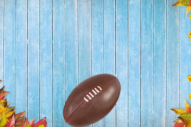 Vista de cima de uma bola de rugby em um piso azul
