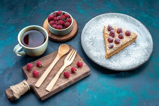 Vista de cima de uma deliciosa fatia de bolo com frutas e uma xícara de chá de açúcar em pó na superfície escura