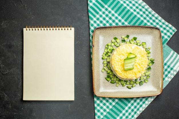 Vista de cima de uma deliciosa salada servida com pepino picado em uma toalha verde despojada e meio dobrada ao lado do caderno em fundo escuro