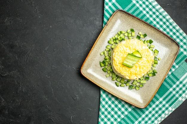 Vista de cima de uma deliciosa salada servida com pepino picado em uma toalha verde despojada e meio dobrada em fundo escuro