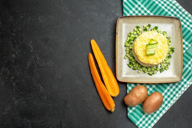 Vista de cima de uma deliciosa salada servida com pepino picado em uma toalha verde despojada pela metade e batatas com cenoura em fundo escuro