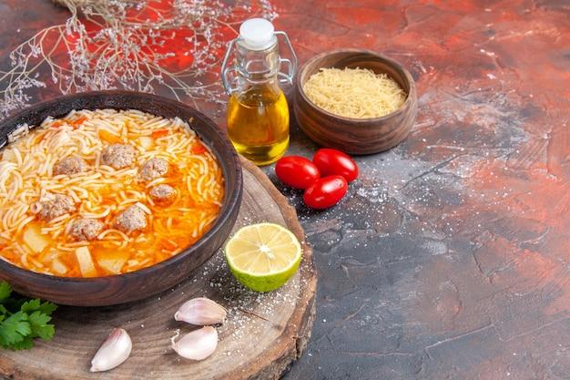 Vista de cima de uma deliciosa sopa de macarrão com frango em tary verdes de madeira garrafa de óleo alho tomate limão em fundo escuro