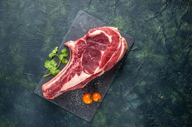 Vista de cima de uma grande fatia de carne crua em uma superfície azul escura