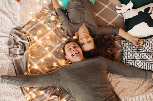 Vista de cima de uma linda mulher e um homem bonito, deitado na cama