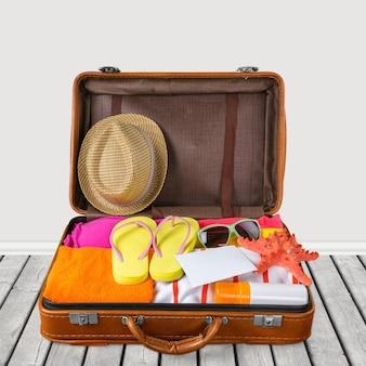 Vista de cima de uma mala aberta cheia de coisas de verão em fundo azul