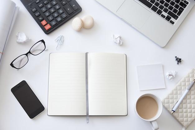 Vista de cima de uma mesa de trabalho com caderno em branco aberto