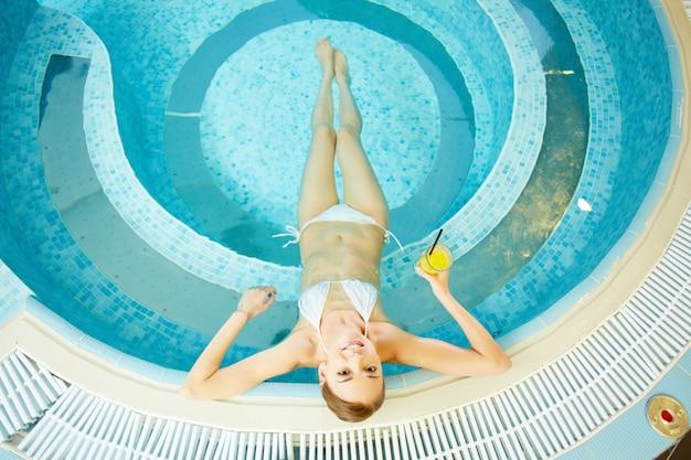 Vista de cima de uma mulher jovem relaxando na água