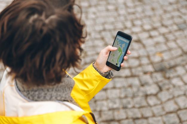 Vista de cima de uma mulher morena perdida em lugar desconhecido, tentando encontrar uma rota usando o mapa on-line em seu gadget