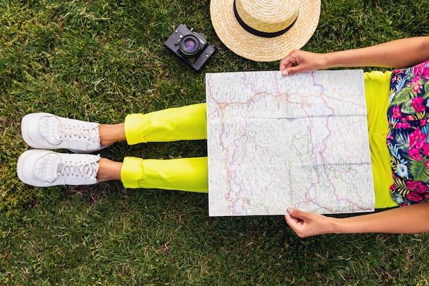 Vista de cima de uma mulher negra com as mãos segurando um mapa, um viajante com uma câmera se divertindo no parque, estilo de moda de verão, roupa colorida hipster, sentado na grama