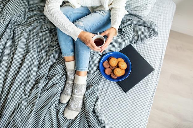 Vista de cima de uma mulher sentada na cama pela manhã, tomando café na xícara, comendo biscoitos, café da manhã