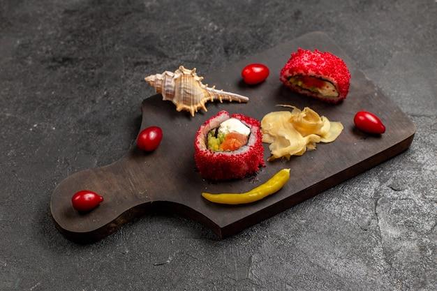 Vista de cima de uma saborosa refeição de sushi em fatias de rolinhos de peixe na parede cinza escuro