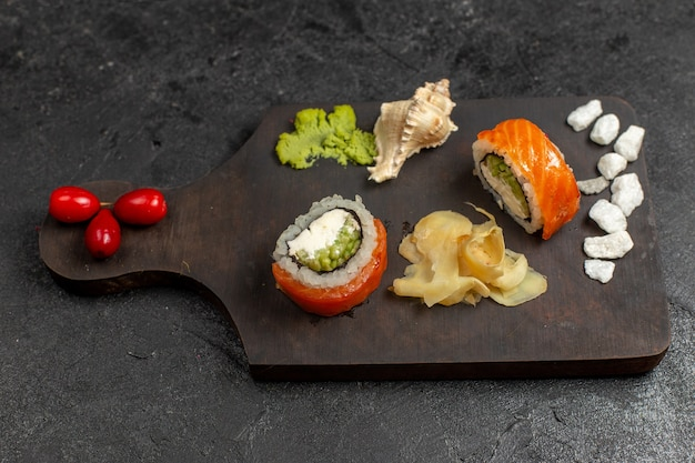 Vista de cima de uma saborosa refeição de sushi em fatias de rolos de peixe com wassabi verde na parede cinza