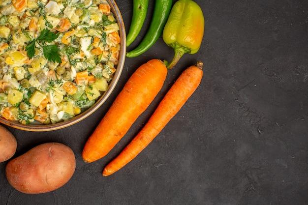 Vista de cima de uma saborosa salada com verduras e legumes em uma mesa escura