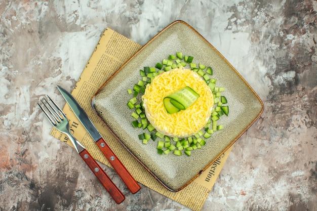 Vista de cima de uma saborosa salada servida com pepino picado e garfo de faca em um jornal velho com fundo de cor mista