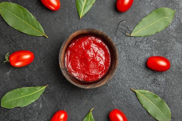 Vista de cima de uma tigela de ketchup ao redor de tomates-cereja e folhas de louro em um solo escuro