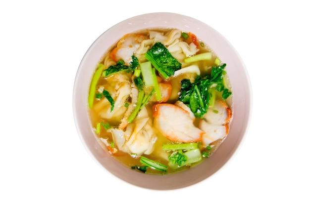 Vista de cima de uma tigela de sopa de bolinho de porco chinês com legumes em fundo branco.
