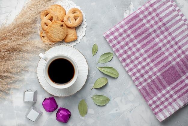 Vista de cima de uma xícara de chá com deliciosos bolinhos de chocolate bombons na luz, biscoito biscoito doce chá açúcar