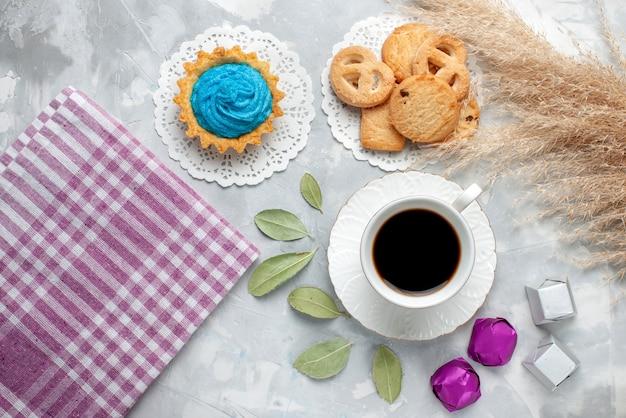 Vista de cima de uma xícara de chá com deliciosos bolinhos de chocolate e biscoitos no chão claro.