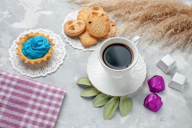 Vista de cima de uma xícara de chá com deliciosos bolinhos de chocolate e bombons na mesa iluminada, bolachas de chocolate e chocolate