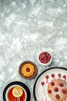 Vista de cima de uma xícara de chá com rodelas de limão e bolo de baga de canela em uma tigela de prato oval com raspberies na superfície cinza copie o local
