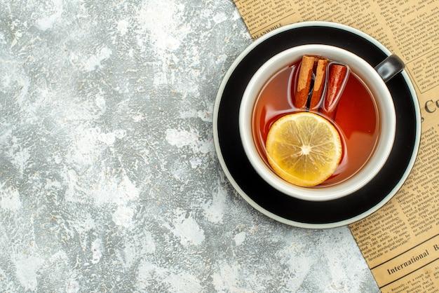 Vista de cima de uma xícara de chá com rodelas de limão e paus de canela no jornal na superfície cinza.