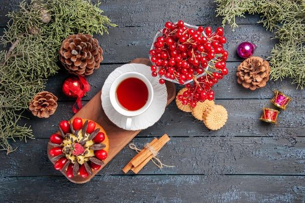 Vista de cima de uma xícara de chá e bolo de frutas vermelhas no prato de servir de madeira groselha em um vidro pinhas brinquedos de natal folhas de pinheiro na mesa de madeira escura