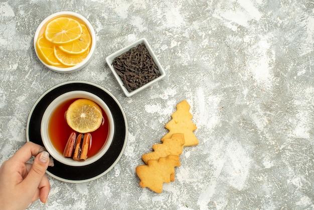 Vista de cima de uma xícara de chá em uma tigela de biscoitos de mão feminina com fatias de chocolate e limão em um espaço livre de superfície cinza