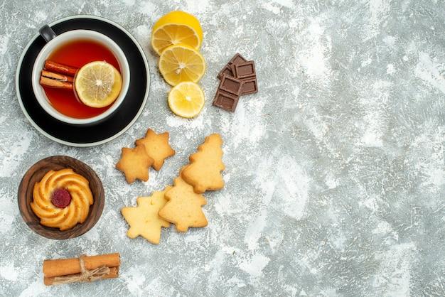Vista de cima de uma xícara de chá, fatias de limão, paus de canela, chocolates, biscoitos, superfície cinza