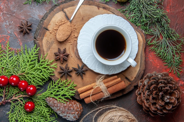 Vista de cima de uma xícara de chá na placa de madeira canela em pau de anis de pinha em fundo escuro
