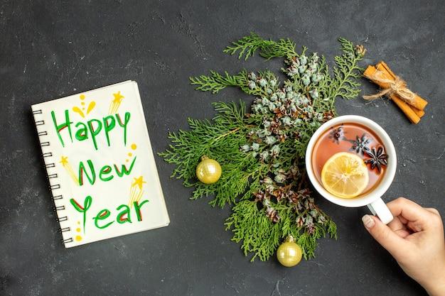 Vista de cima de uma xícara de chá preto com acessórios de natal e limão com canela e caderno com a inscrição de feliz ano novo em fundo preto
