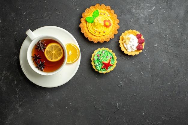Vista de cima de uma xícara de chá preto com limão servido com biscoitos em fundo escuro