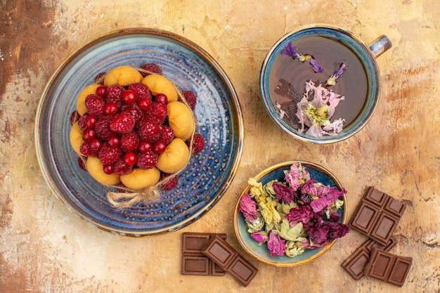 Vista de cima de uma xícara de chá quente de ervas, bolo macio com barras de chocolate de frutas e flores