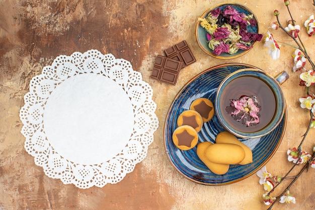 Vista de cima de vários biscoitos, uma xícara de chá e barras de chocolate de flores na mesa de cores misturadas