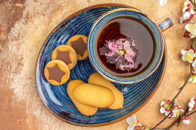 Vista de cima de vários biscoitos, uma xícara de chá e flores na mesa de cores misturadas