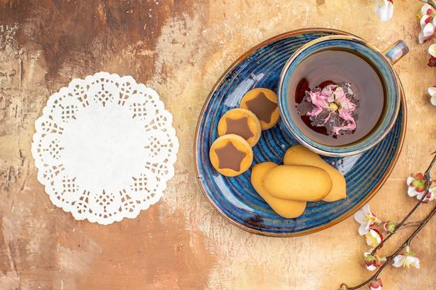 Vista de cima de vários biscoitos, uma xícara de flores de chá e um guardanapo na mesa de cores misturadas