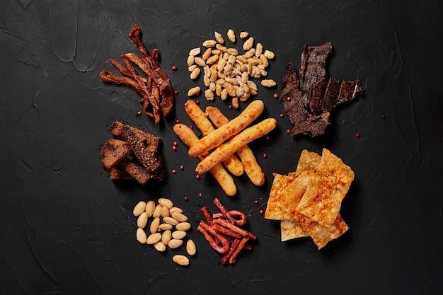 Vista de cima de vários petiscos de cerveja, como biscoitos de amendoim, salsichas, chips de queijo seco em uma mesa escura