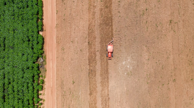 Vista de cima de veículos agrícolas trator trabalhando no campo