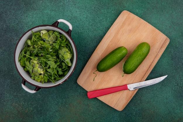 Vista de cima de verduras em uma panela com pepinos em uma tábua com uma faca em um fundo verde