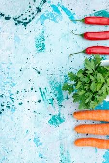 Vista de cima de verduras frescas isoladas dentro do prato com pimentas vermelhas picantes alinhadas e cenouras em uma refeição de produto de folha verde azul brilhante