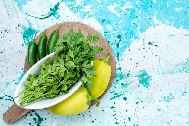 Vista de cima de verduras frescas isoladas dentro do prato, juntamente com pimentões verdes e pimentas picantes em uma refeição de produto de folha verde azul brilhante