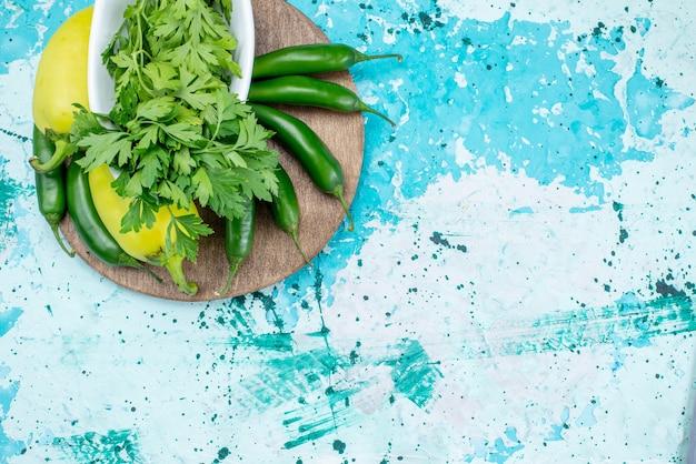 Vista de cima de verduras frescas isoladas dentro do prato junto com pimentões verdes e pimentões picantes em uma mesa azul brilhante, produto de folha verde comida refeição vegetal