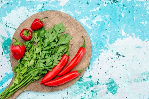 Vista de cima de verduras frescas junto com pimentas vermelhas picantes no ingrediente alimentar verde vegetal, azul brilhante