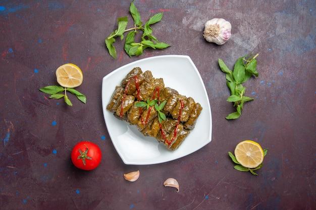Vista de cima deliciosa folha de dolma carne moída prato dentro da placa no fundo escuro carne prato folha comida jantar