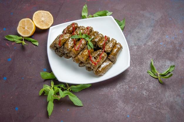 Vista de cima deliciosa folha de dolma carne moída prato dentro da placa no fundo escuro carne prato folha comida jantar Foto gratuita